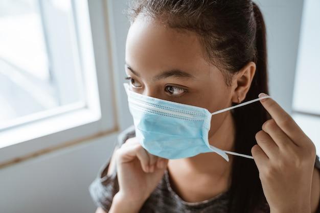 Asiatisches junges mädchen trägt eine medizinische maske, während es am fenster sitzt