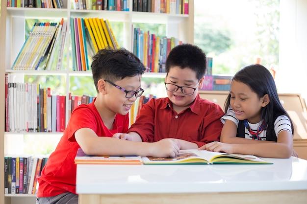 Asiatisches junges mädchen u. jungen, die bücher auf schreibtisch und glück lesen, fühlen an der bibliothek in ihrer schule
