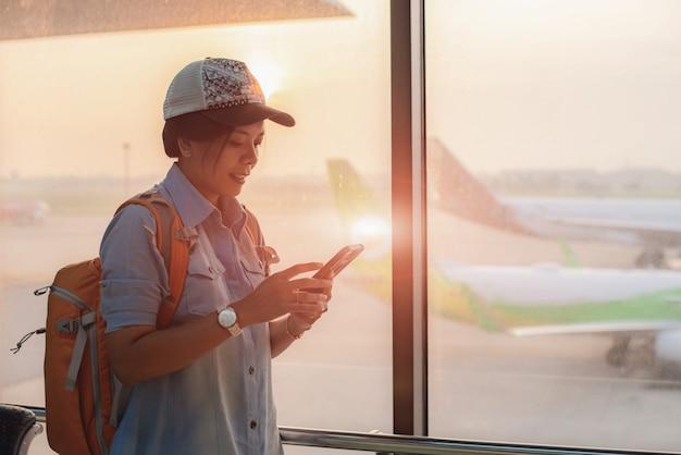 Asiatisches junges mädchen überprüfen flug und überprüfen herein flug unter verwendung des internets im telefon.