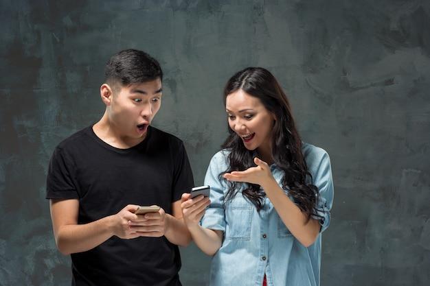 Asiatisches junges paar, das handy, nahaufnahmeporträt verwendet.