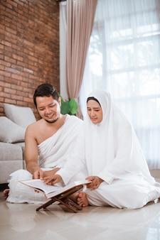 Asiatisches junges paar, das mit al-qur'an und gebetsperlen betet