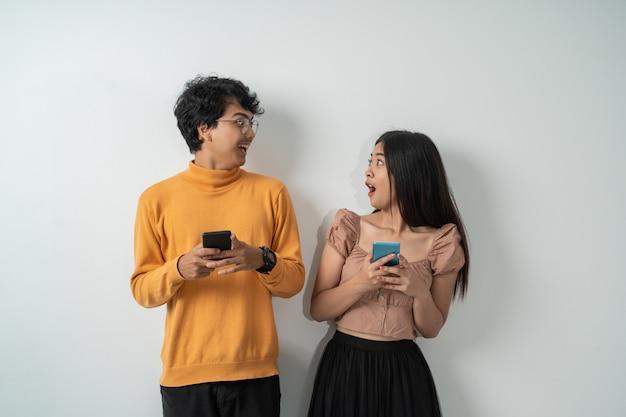 Asiatisches junges paar mit einem überraschten ausdruck, während sie ihre smartphones benutzen