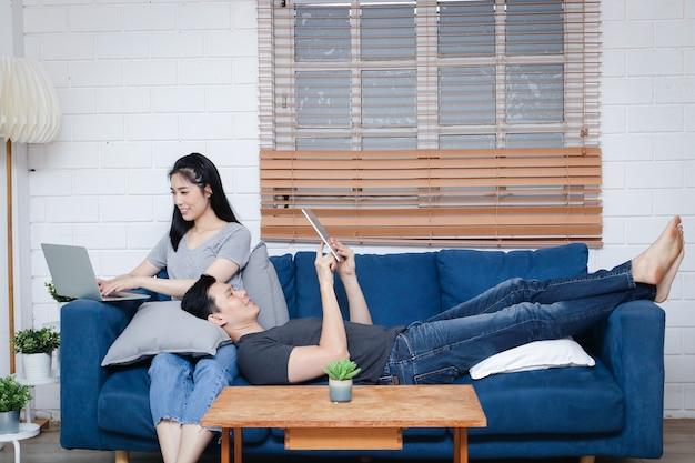 Asiatisches junges paar sitzen sie und entspannen sie sich auf ihrem blauen sofa in ihrem haus während der ferien