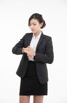 Asiatisches junges schönes geschäftsfrauenkleid im schwarzen anzug und im kurzen rock mit kluger uhr