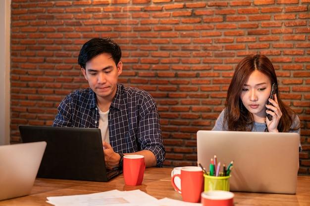 Asiatisches junges startup-business-team in freizeituniform, das im modernen büro für arbeitsräume diskutiert und zusammenarbeitet.