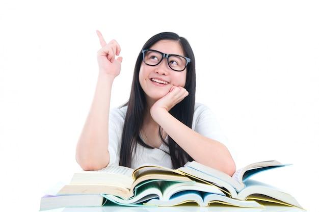 Asiatisches junges studentenmädchen, das mit buch über weißem hintergrund denkt
