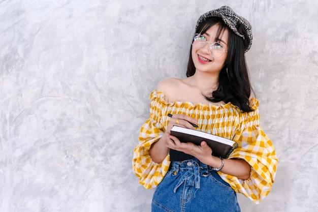 Asiatisches junges studentinpositiv attraktiv auf wandhintergrund