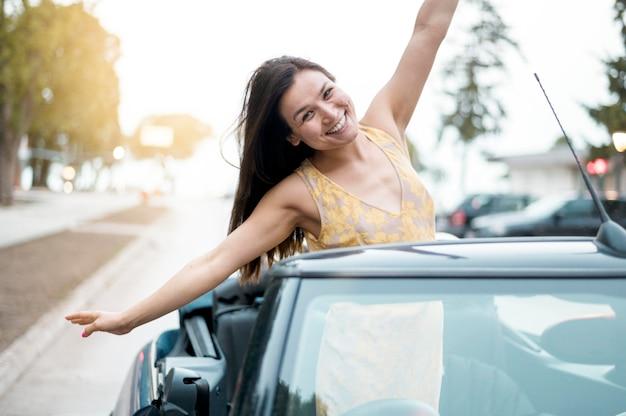 Asiatisches junges weibliches modell, das ein auto reitet