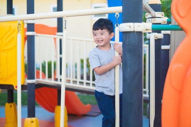 Asiatisches kind, das am spielplatz unter dem sonnenlicht im sommer, im glücklichen kind im kindergarten oder im vorschulschulhof spielt.