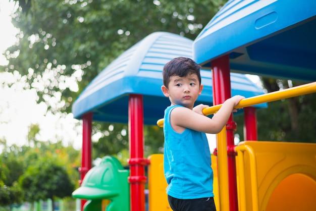Asiatisches kind, das am spielplatz unter dem sonnenlicht im sommer spielt