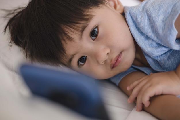 Asiatisches kind, das auf bett liegt und am handy spielt