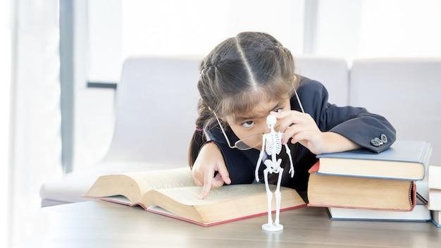 Asiatisches kind, das biologische wissenschaft auf buch mit skelettmodell lernt