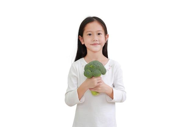 Asiatisches kind, das brokkoli auf weiß hält. fokus im gesicht