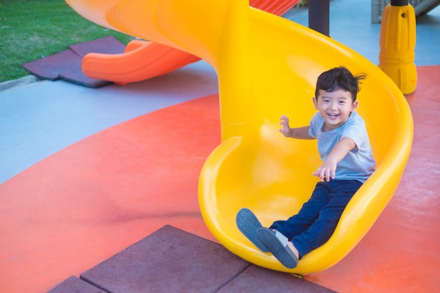 Asiatisches kind, das dia am spielplatz spielt