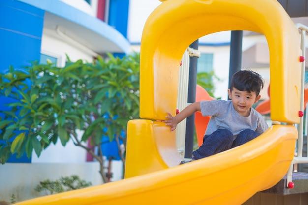 Asiatisches kind, das dia am spielplatz unter dem sonnenlicht im sommer, im glücklichen kind im kindergarten oder im vorschulschulhof spielt.