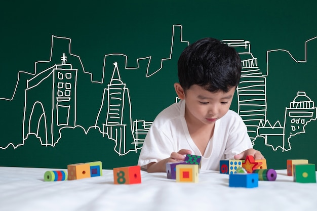 Asiatisches kind, das durch das spielen mit seiner fantasie über gebäude- und ingenieurarchitekturzeichnung und -designer lernt