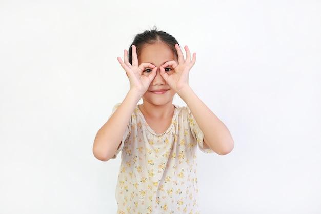 Asiatisches kind, das durch imaginäres fernglas auf weiß schaut