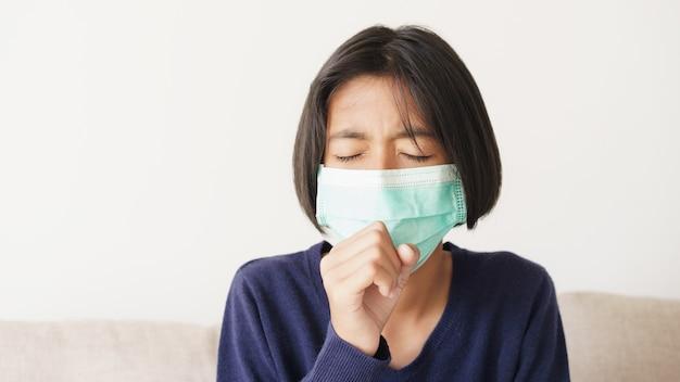 Asiatisches kind, das eine schutzmaskenepidemie der grippe oder der covid-19 im wohnzimmer zu hause trägt