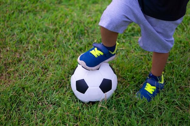 Asiatisches kind, das fußball oder fußball im park spielt