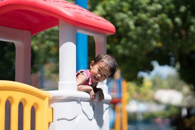 Asiatisches kind, das im spielplatz spielt