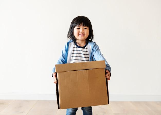 Asiatisches kind, das jetzt hilft, haus zu bewegen