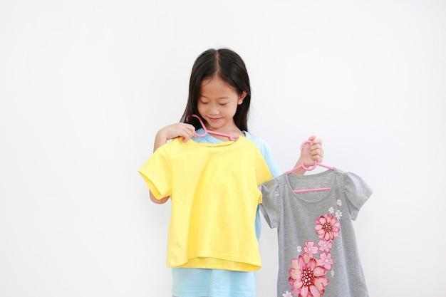 Asiatisches kind, das kleidung auf weiß wählt