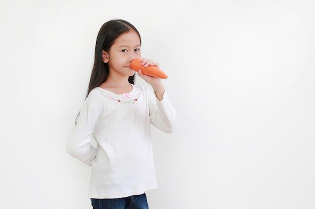 Asiatisches kind, das lange nase mit karotte auf weiß macht