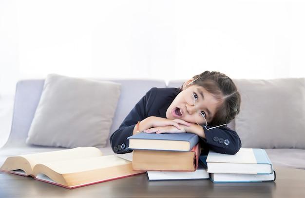 Asiatisches kind, das lesendes lehrbuch über bildungskonzept lernt