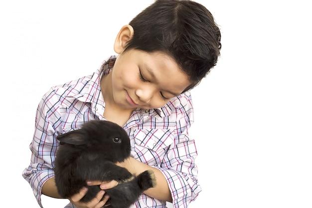 Asiatisches kind, das mit dem reizenden babykaninchen lokalisiert über weiß spielt
