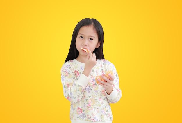 Asiatisches kind, das orange frucht auf gelb isst
