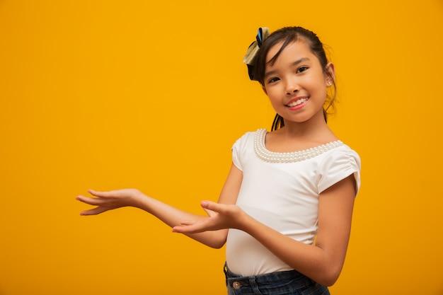 Asiatisches kind, das produkt auf gelbem hintergrund darstellt