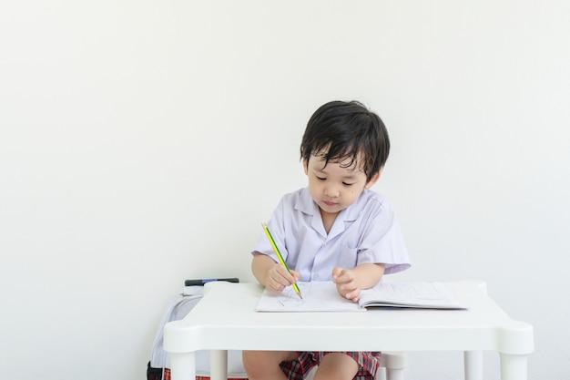 Asiatisches kind, das sitzt, um hausaufgaben nach der schule zu erledigen