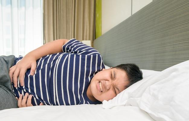 Asiatisches kind, das unter bauchschmerzen leidet und auf bett liegt. durchfall oder gesundes konzept
