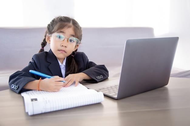 Asiatisches kind, das vom digitalen klassenzimmer durch internet und drahtlose technologie lernt