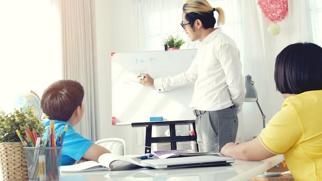 Asiatisches kind, das zu hause mit lehrer lernt.