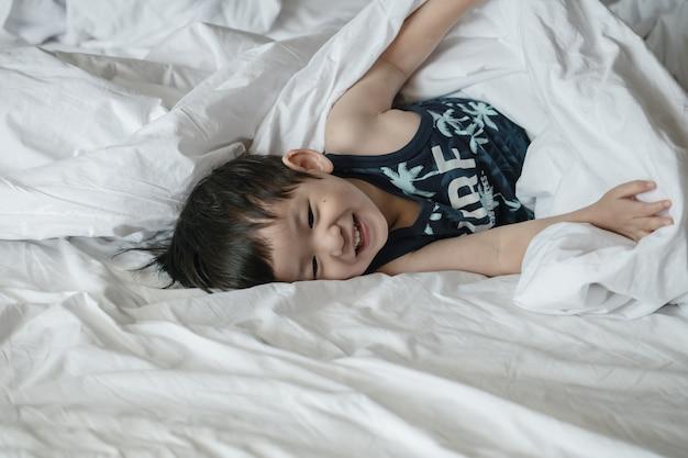 Asiatisches kind der nahaufnahme auf bett mit spaßbewegung morgens