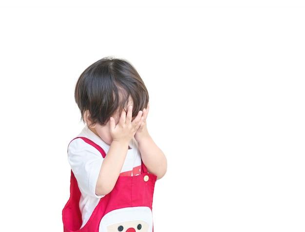 Asiatisches kind der nahaufnahme benutzen ihre hände, um ihre augen zu schließen, die auf weißem hintergrund lokalisiert werden