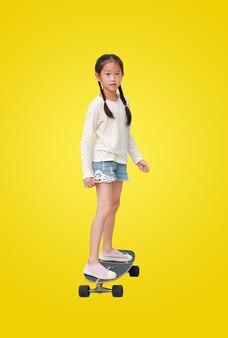 Asiatisches kind des kleinen mädchens, das auf einem skateboard lokalisiert auf gelbem hintergrund skatet. kinderreiten auf skateboard. bild mit beschneidungspfad