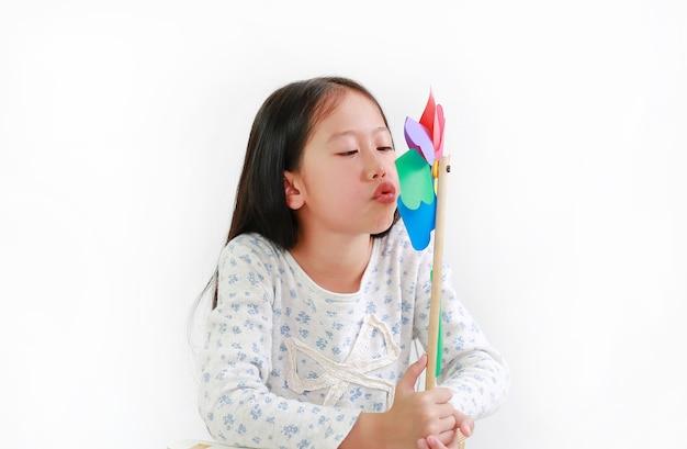 Asiatisches kind des kleinen mädchens, das buntes windrad über weißem hintergrund durchbrennt. kinder halten und spielen windmühle in der hand