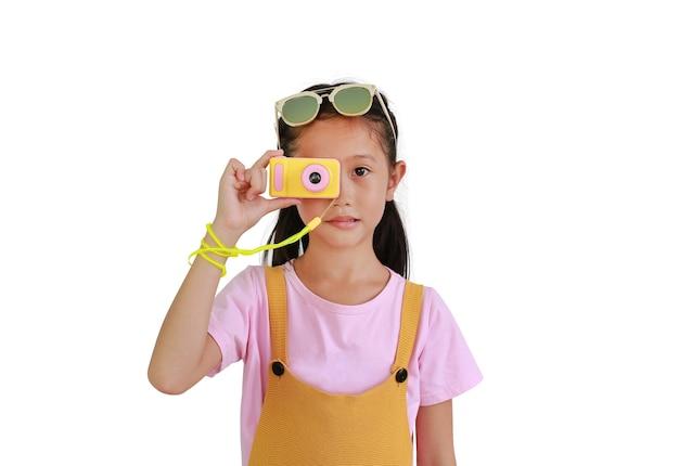 Asiatisches kind des kleinen mädchens, das foto mit der fotokamera lokalisiert auf weißem hintergrund macht. bild mit beschneidungspfad