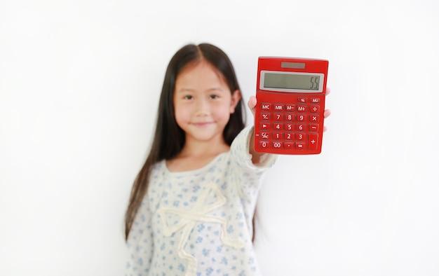 Asiatisches kind des kleinen mädchens, das rechner über weißem hintergrund zeigt. kind, das einen roten taschenrechner hält selektiver fokus bei calc