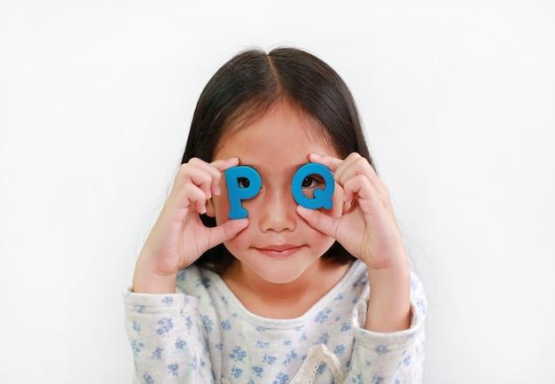 Asiatisches kind des kleinen mädchens, das text des alphabetes pq (positive intelligenz) auf augen über weißem hintergrund hält. bildungskonzept