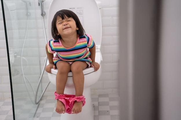 Asiatisches kind drückt es hart, während es auf der toilette sitzt
