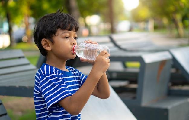 Asiatisches kind durstiges wasser und trinkwasser von einer transparenten plastikflasche im park.