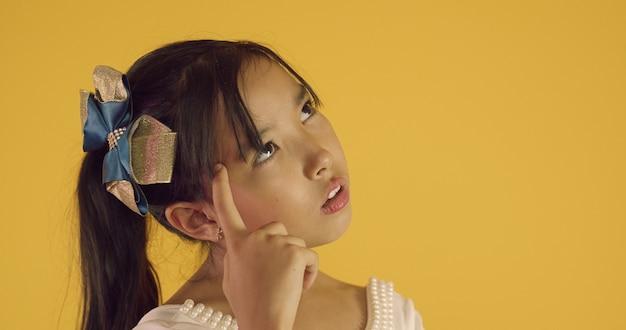Asiatisches kind hat eine idee. japanisches kind, das auf den kopf zeigt. hatte eine tolle idee. japanisches kinderdenken.