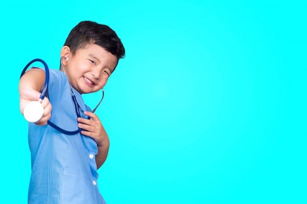 Asiatisches kind in der blauen medizinischen uniform, die stethoskop hält.