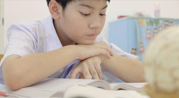 Asiatisches kind in der studentenuniform, zum der hausarbeit zu hause zu tun.