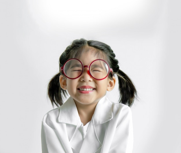 Asiatisches kind in weißer uniform wie doktor oder erfinder glückliche aktion mit glas