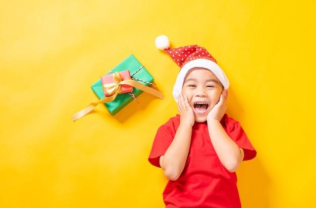 Asiatisches kind liegendes lächeln im gekleideten roten weihnachtsmann das konzept des feiertagsweihnachtstages