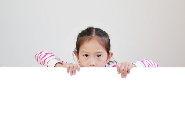 Asiatisches kind mit leerem brett für ihren text auf weiß